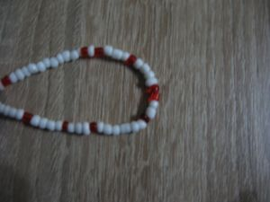 Нанизана гривна с бели и червени камъчета и синьо топче-мин.количество 10 бр.